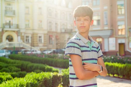 Outdoor portrait of teenager 13, 14 years old, boy with crossed arms, urban background.