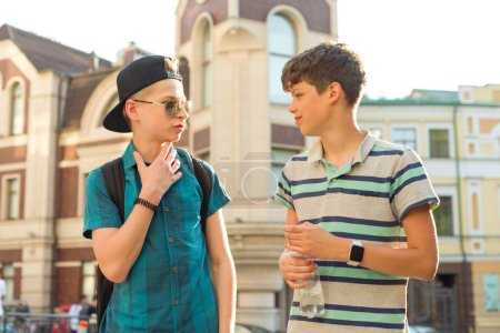 The friendship and communication of two teenage boys is 13, 14 years old, city street background.