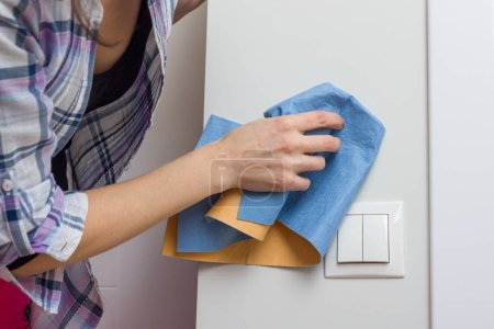 Photo for Female cleans a dirty wall at home with professional rag. - Royalty Free Image