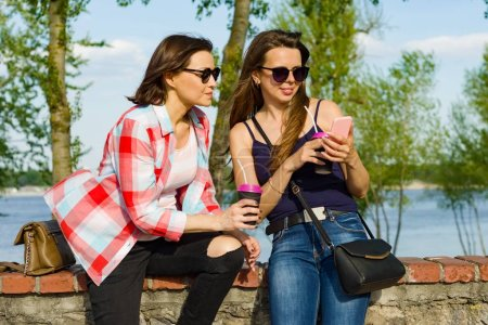 Photo for Outdoors portrait of female friends drinking coffee and having fun. Background nature, park, river. Urban lifestyle and friendship concept - Royalty Free Image