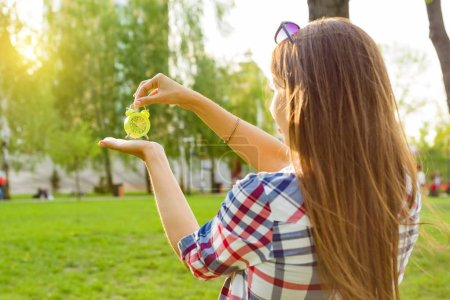 Photo for Young woman holding alarm clock in her hand, looking at the time. Background sunny city park, copy space - Royalty Free Image