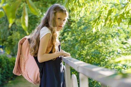 Girl schoolgirl blonde with backpack in school uniform near fence in the school yard, back to school.