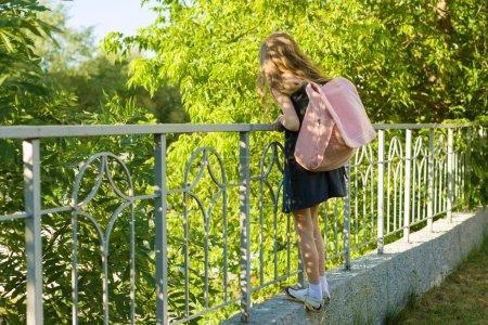 Photo pour Blonde écolière fille avec sac à dos en uniforme scolaire près de clôture dans l'yard de l'école, retour à l'école. - image libre de droit