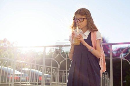 Foto de Retrato al aire libre de estudiantes de escuela primaria chica con gafas, uniforme escolar, con mochila beber zumo natural de vidrio. Copia espacio - Imagen libre de derechos
