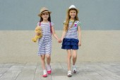 Outdoor summer portrait of two happy girl friends 7, 8 years holding hands. Girls in striped dresses, hats with backpack, background gray wall