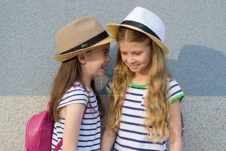 Photo pour Portrait d'estivales en plein air de deux amis fille heureux 7, 8 ans dans le profil de parler et rire. Filles en robes rayés, chapeaux avec sac à dos, fond mur gris - image libre de droit