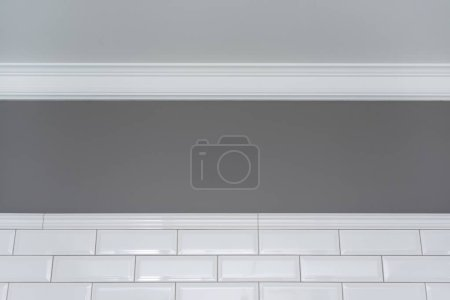 Photo for Gray painted wall, white ceiling molding and ceramic decorative tiles small white glossy brick. Fragment of the walls of the bathroom, toilet, kitchen. Interior details close-up. - Royalty Free Image