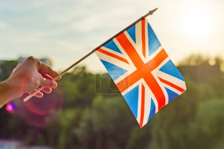 Hand holds Great Britainin flag an open window. Background blue sky, silhouette of the city, sunset.