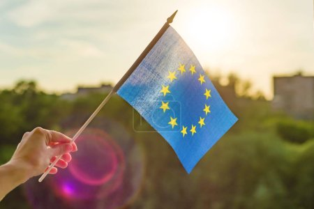 Photo for Hand holds European Union flag in an open window. Background blue sky, silhouette of the city, sunset. - Royalty Free Image