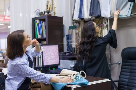 Photo pour Femelle concepteur, décorateur, propriétaire du magasin montre le tissu. Magasin de textile de petite entreprise - image libre de droit