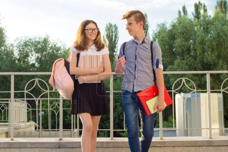 Photo for Children teenagers with backpacks, textbooks, notebooks go to school, back to school - Royalty Free Image