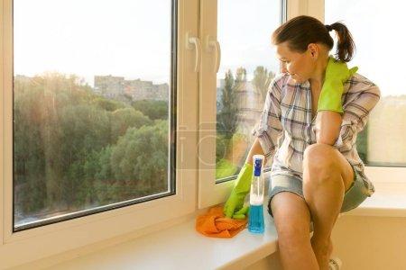Foto de Mujer con guantes de goma, trapo y rociador de detergente se ve en la ventana de lavado limpiarla - Imagen libre de derechos