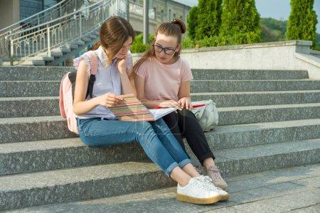 Photo pour Portrait de deux écolières des adolescents des sacs d'école et des livres. Parler, apprendre. - image libre de droit