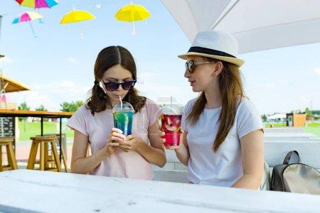 Photo pour Filles ados en chapeau et des lunettes de soleil sur la terrasse profitant de leurs cocktails - image libre de droit