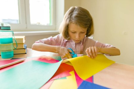 Photo for School, education, knowledge and children. Pupil of elementary school girl sitting at table cutting out colored paper - Royalty Free Image