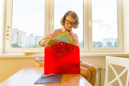 Photo for Little girl is packing his school backpack sitting on the desk. School, education, knowledge and children - Royalty Free Image