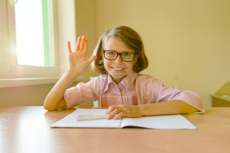 Photo for Small student in glasses sits at a desk with a notebook raised her hand showing 5 fingers. School, education, knowledge and children - Royalty Free Image