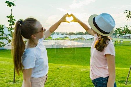 Foto de La amistad de dos adolescentes, novias mejor divertirán en la naturaleza, en el verde césped del parque de recreación y entretenimiento, mostrar las manos en el corazón de fondo puesta de sol en el Parque - Imagen libre de derechos