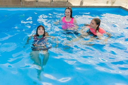 Photo for Group of 3 teenage girlfriends having fun in swimming pool - Royalty Free Image