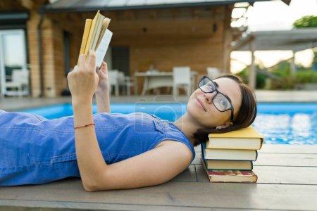 Photo pour Jeune fille dans des lunettes près de la piscine avec une pile de livres, livre de lecture. Éducation, été, connaissance - image libre de droit