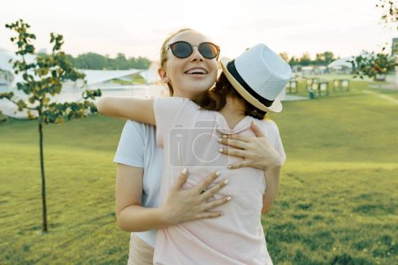 Photo for The friendship of two teenage girls, best girlfriends have fun in nature, on the green lawn of recreation park and entertainment. Embrace the greeting and parting - Royalty Free Image