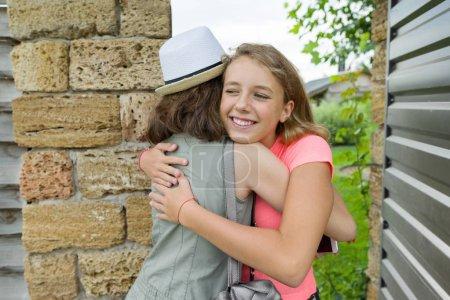 Photo pour Jeune fille ouvre la porte d'entrée, copines accueillis, embrassades lors de la réunion - image libre de droit