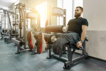 Photo for Athletic muscular bearded exercising man at the modern sport gym. Fitness, sport, training, people concept. - Royalty Free Image