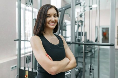Photo for Young athletic confident woman fitness instructor posing in gym with folded crossed arms, looking in camera. - Royalty Free Image