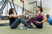 """Постер, картина, фотообои """"Две молодые здоровые женщины вместе упражнения в тренажерном зале. Фитнес, спорт, обучение, люди, концепция здорового образа жизни."""""""