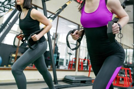 Photo for Group training with fitness loops in the gym, two young attractive athlete women doing crossfit with straps system. Sport, teamwork, training, people concept - Royalty Free Image