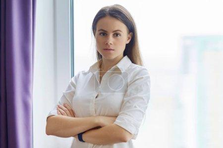 Photo pour Portrait de jeune femme confiante avec les bras croisés près de la fenêtre de bureau, femme regardant en souriant de la caméra. - image libre de droit