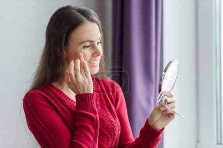 Photo for Young smiling woman with face moisturizer near eyes, female holding face cream, standing near window with mirror. Youth and skin care concept. - Royalty Free Image