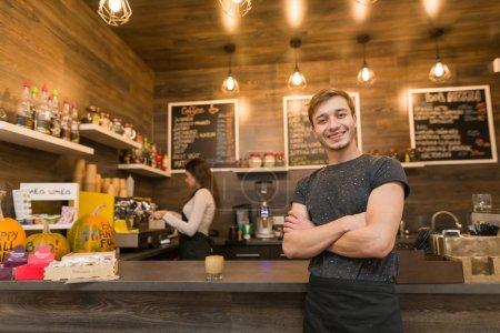 Photo pour Portrait de souriant jeune homme café propriétaire, femme confiante avec les bras croisés debout au comptoir avec barista travaille en arrière-plan, fabrication de boissons. - image libre de droit