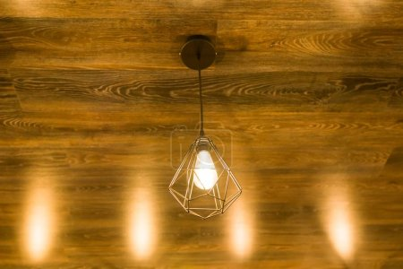 Photo pour Lampe géométrique moderne et élégante sur un plafond en bois brun bronze . - image libre de droit