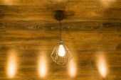 Modern stylish geometric lamp on a bronze brown wooden ceiling