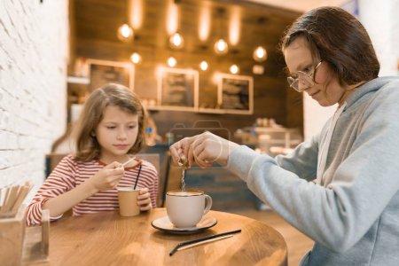 Photo pour Enfants de deux jeunes filles dans un café, boire une boisson de lait. - image libre de droit
