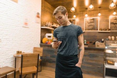 Photo pour Jeune homme dans tablier cafetière travailleur au comptoir du bar, la prise de commande sur smartphone . - image libre de droit