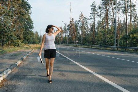 Photo pour Femme d'âge mûr marchant le long de la route, en regardant la route. - image libre de droit