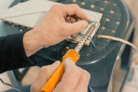 Photo for Male holding soldering iron tool repairing, electrical wire connection, soldering with a soldering iron. - Royalty Free Image