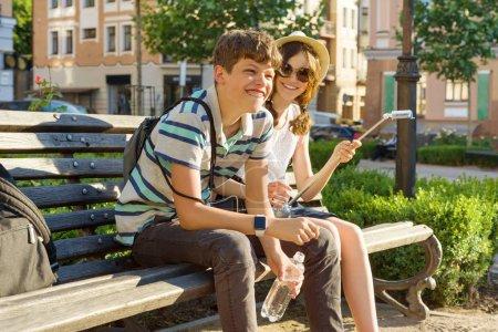 Photo pour Fille et garçon d'amis d'adolescent s'asseyant sur le banc dans la ville, souriant, parlant, regardant dans le téléphone. Concept d'amitié et de personnes. - image libre de droit