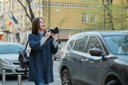 Photo pour Belle jeune femme avec l'appareil-photo dans la ville. Fille de touriste voyageant et photographiant, fond de rue de ville de ressort. - image libre de droit