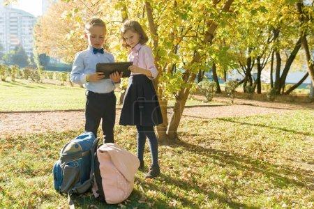 Photo pour Deux enfants regardant tablette numérique, fond automne parc ensoleillé, heure d'or - image libre de droit