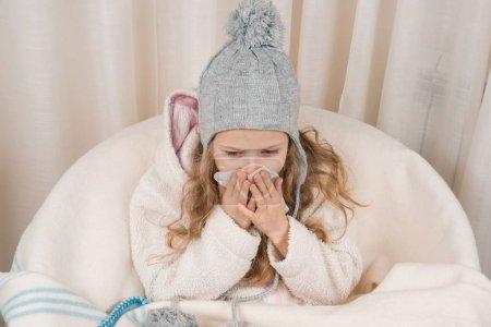 Photo pour Enfant fille à la maison dans la chaise avec chapeau chaud en laine couverture éternuements en mouchoir. Saison automne hiver rhumes . - image libre de droit