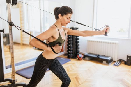 Woman training arms with fitness straps in the gym Concept workout healthy lifestyle sport
