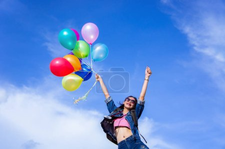 Photo pour La fille sauteuse tient une boule de couleur claire sur un fond de ciel lumineux - image libre de droit
