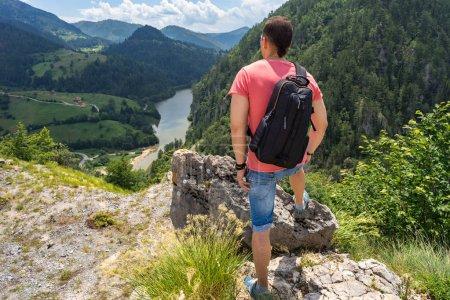 Foto de Turista con pie de mochila de montaña de hombre y mirar en Spajici lago y cerros de las altas en el Parque Nacional de Tara en Zaovine, Serbia - Imagen libre de derechos