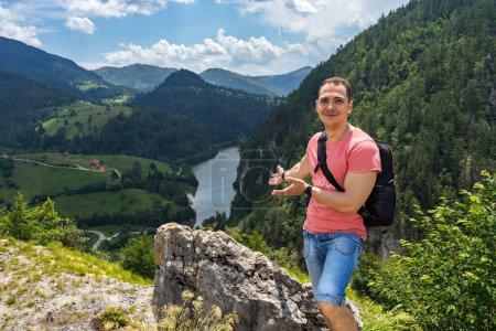 Foto de Turístico de hombre sonriente con la situación de la mochila en la montaña con hermosa vista desde la altura en el Parque Nacional de Tara en Zaovine, Serbia - Imagen libre de derechos