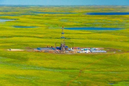 Photo pour Appareil de forage et équipement dans un champ pétrolifère de la toundra du Nord. Vue de dessus depuis un hélicoptère. Toundra estivale verte avec lacs au-delà du cercle polaire arctique . - image libre de droit