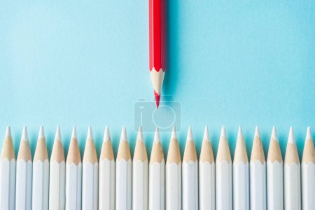 Photo for Business concept - lot of white pencils and color pencil on blue paper background. It's symbol of fight, leadership and communication. - Royalty Free Image