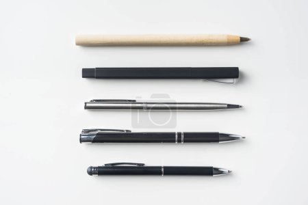 Photo for Top view of collection of pens on white background desk for mockup - Royalty Free Image